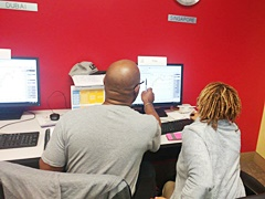 A man and woman discussing a trade in class at Online Trading Academy