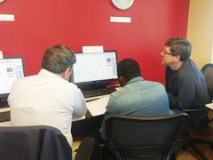 3 men discussing a trade in class at Online Trading Academy
